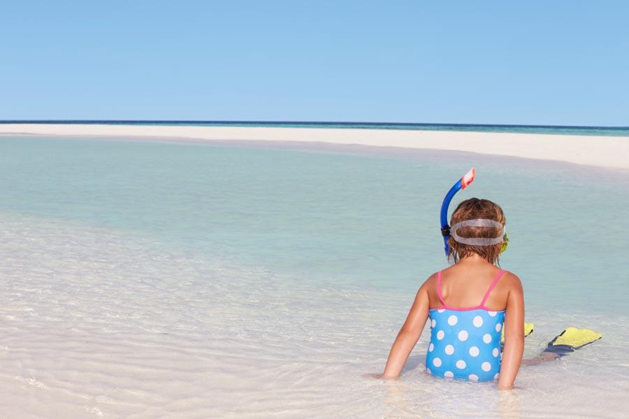 Kind sitzt mit Schnorchelset am Strand